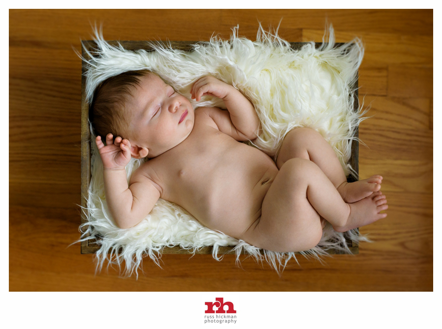 A Newborn Baby sleeps in a rustic box on fur in Philadelphia Newborn Photography Session.