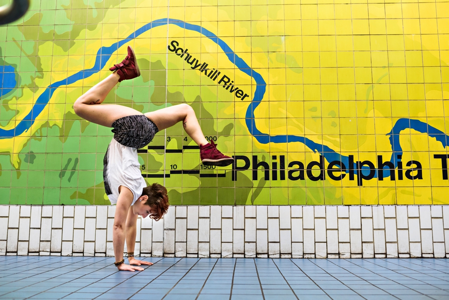 A woman doing a handstand in front of a map of philadelphia in the subway.