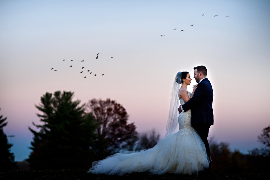 A bride and groom hug in the sunset on the golf course of Northampton Valley Country Club.