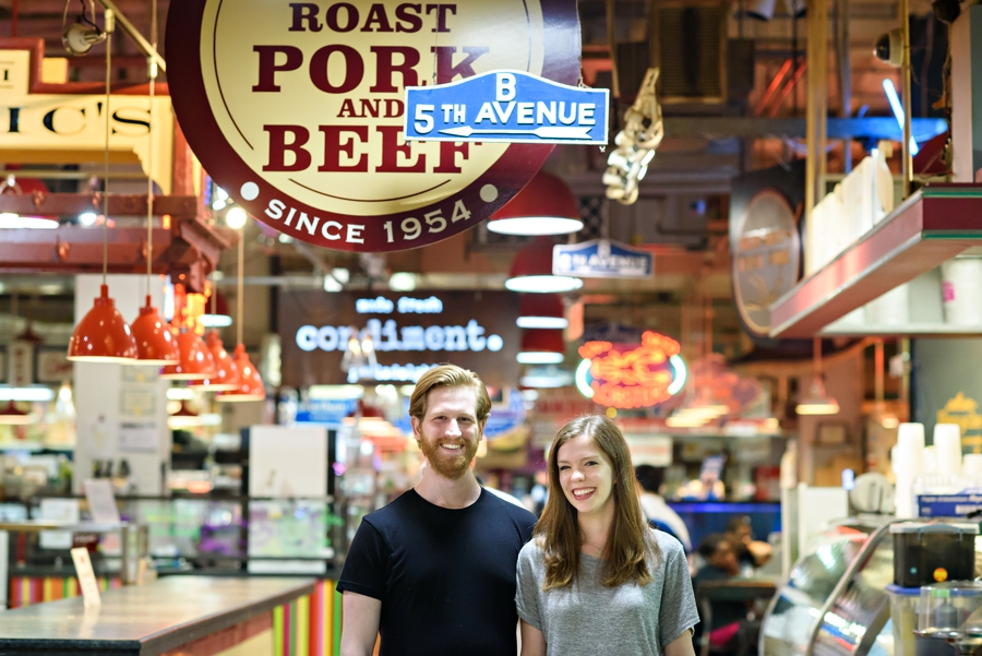 An engaged couple standing in Reading Terminal Market in Philadelphia during thier engagement Session.