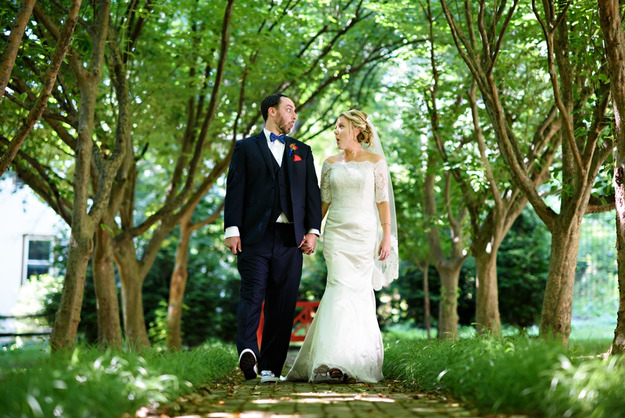 A married couple walk along a tree lined walkway and make silly faces after their wedding at Appleford Esatates in Villanova, PA.