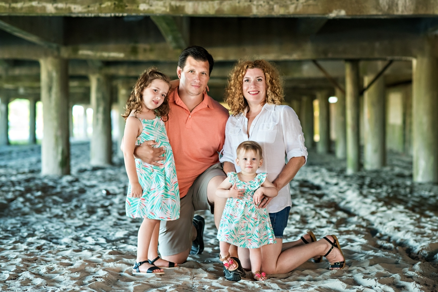 A family pose for a portrait under the boardwalk in Wildwood, NJ.