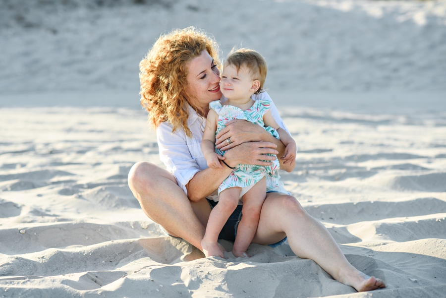 A mother holding her baby while they sit on the beach in Wildwoon, NJ during thier Family Photography Session.