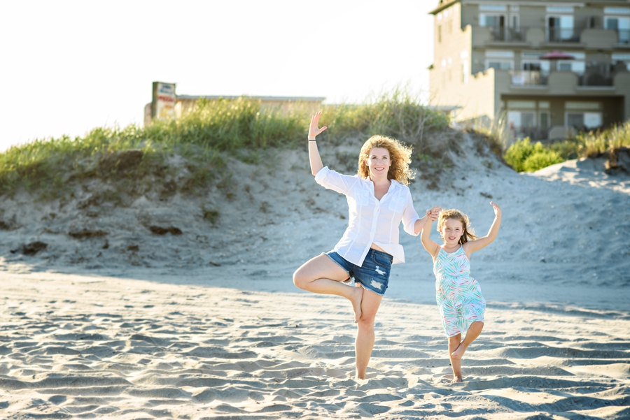 A mom and her daughter do yoga on the beach of Wildwood, NJ during their family photography session.
