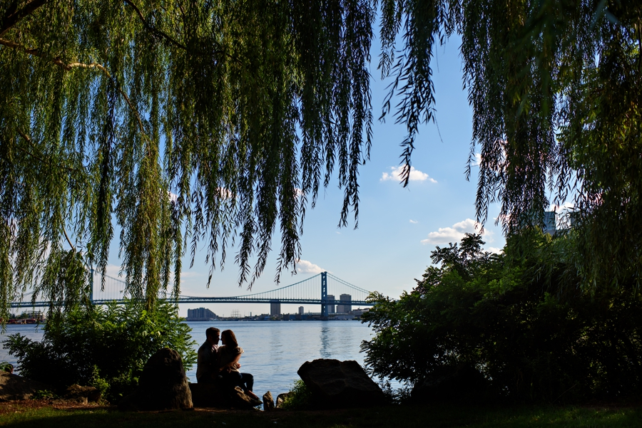 A silhouette of a couple in Penn Treaty Park with the Ben Franklin Bridge in the background during their Philadelphia Engagement Session.