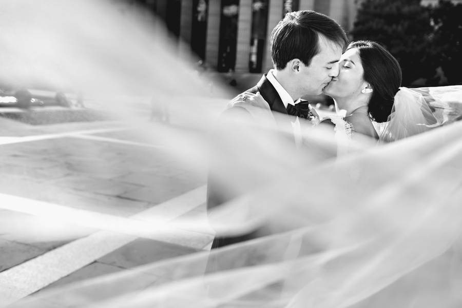 A bride and groom kiss on the Philadelphia Museum of Art steps with the brides full cathedral veil blowing in the wind during the Union League of Philadelphia Wedding.