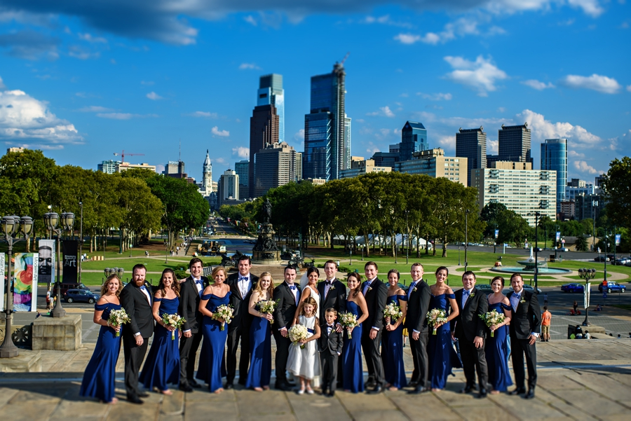 A large wedding party standing on the Philadelphia Art Museum steps with the Philly Skyline in the background during the Union League of Philadelphia Wedding.