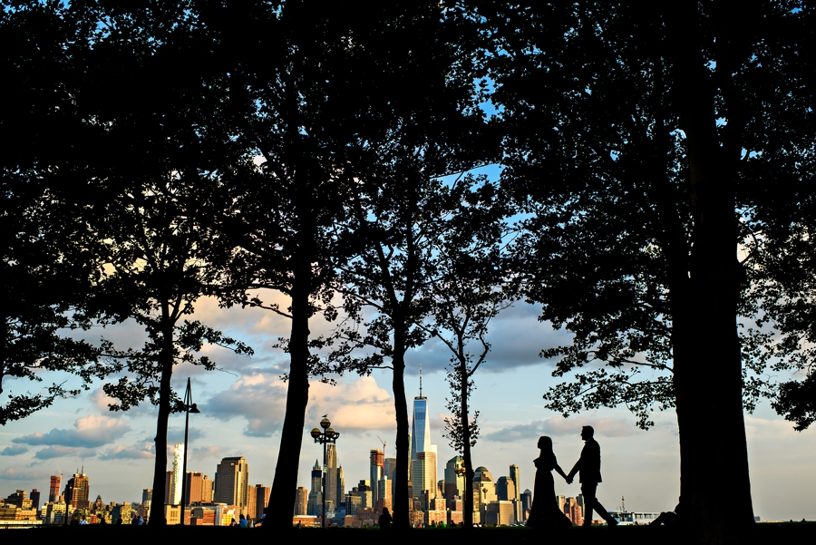 A bride to be and her fiance walk along the trees with the New York City Skyline in the background for their Hoboken Engagement Session.