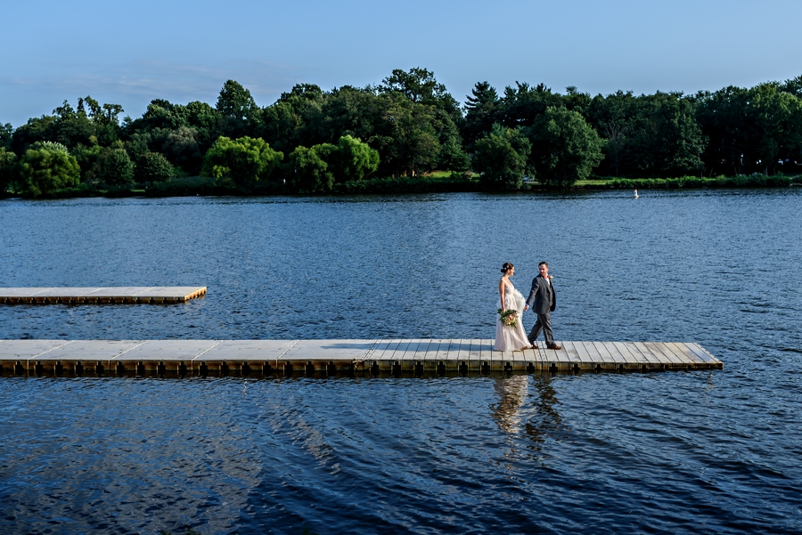 A married couple walk to the end of the dock on their wedding at the Camden County Boathouse in Pennsauken, NJ.