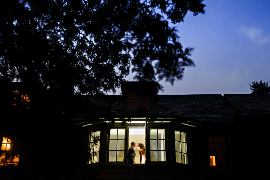 A newly married couple sit in the window of a mansion in merion station PA at sunset after thier wedding.