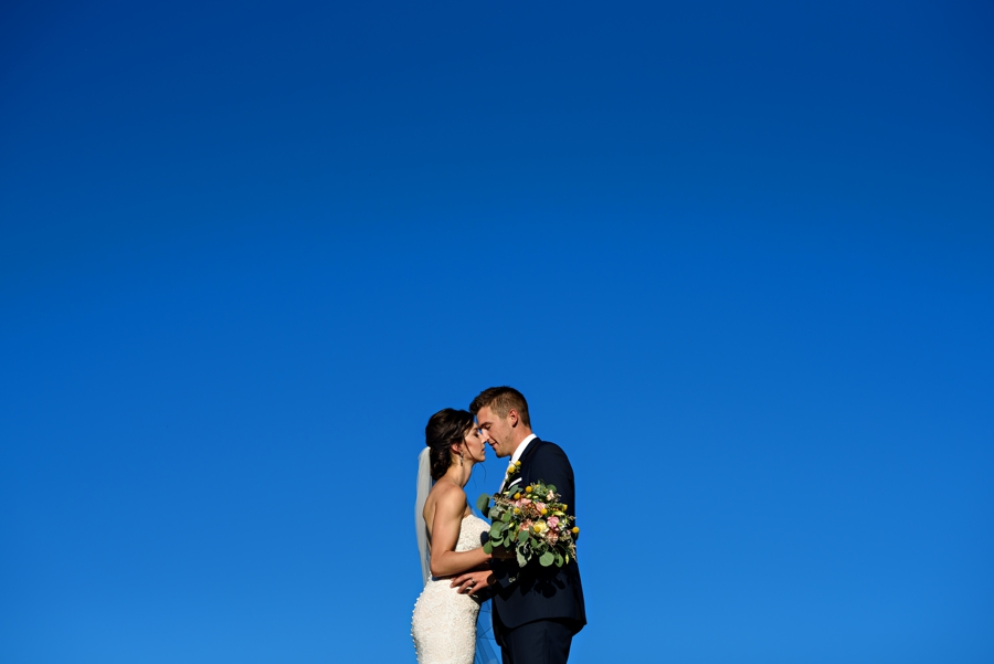 A newly married couple kiss under a blue sky at their Stoltzfus Homestead Wedding.