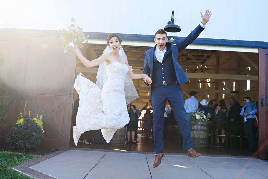A bride and Groom jump in the air coming out of the barn after the wedding ceremony at Stoltzfus Homestead and Gardens.