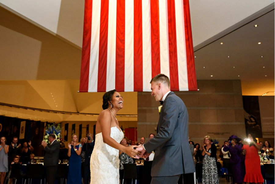 A newly married couple having their first dance under the american flag at their National Constitution Center Wedding.