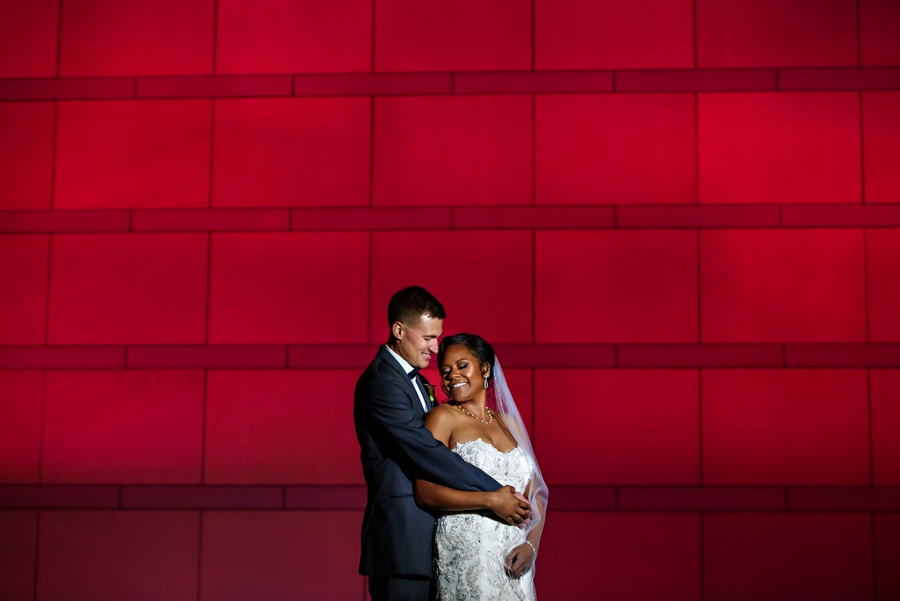 A bride and Groom hold each other in front of a colorful wall after their wedding at The National Constitution Center.