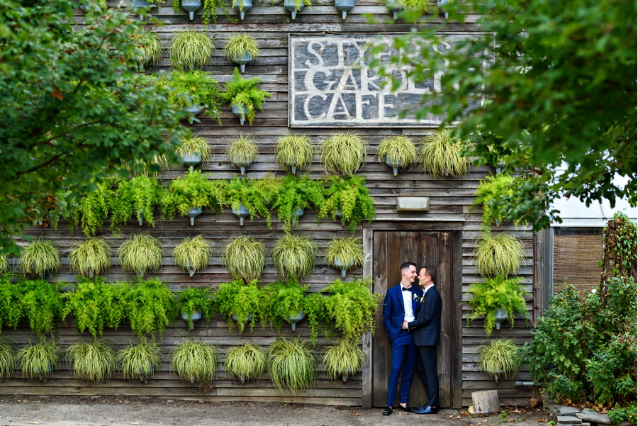 A same sex couple hold each other in front a wall of green plants at their wedding at Terrain at Styers in Glen Mills, PA.