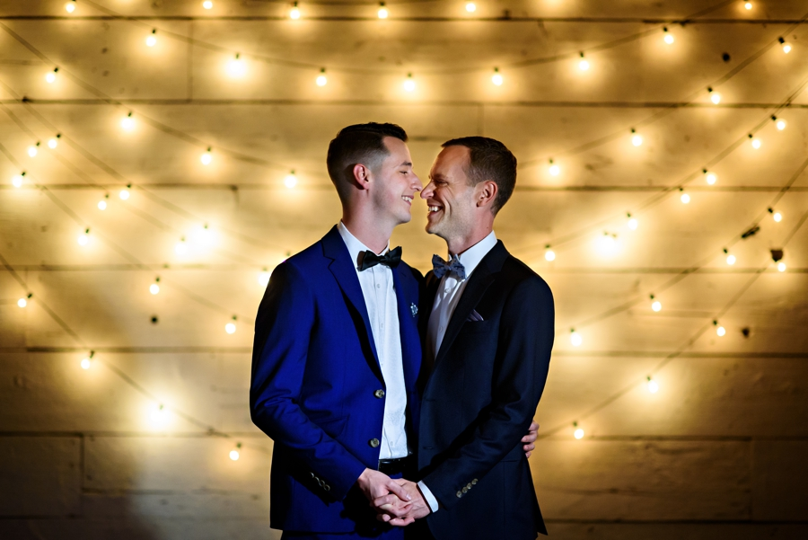 Two grooms laugh and hug after their wedding ceremony at Terrain at Styers in Glen Mills, PA.