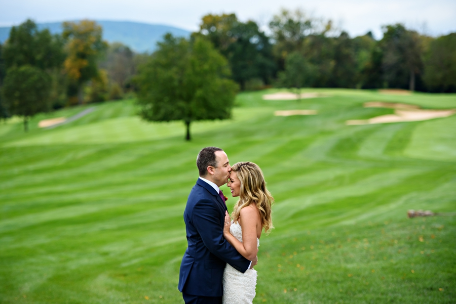 A groom holds his bride and kisses her forhead on the golf course at Lehigh Country Club.