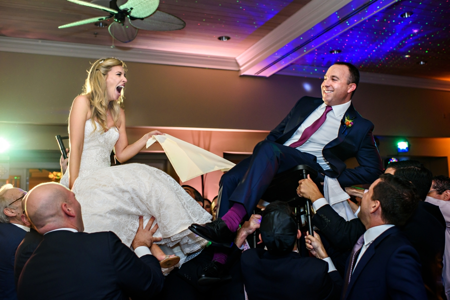 A newly married couple are lifted up in chairs during the Horah at their Lehigh Country Club Wedding.