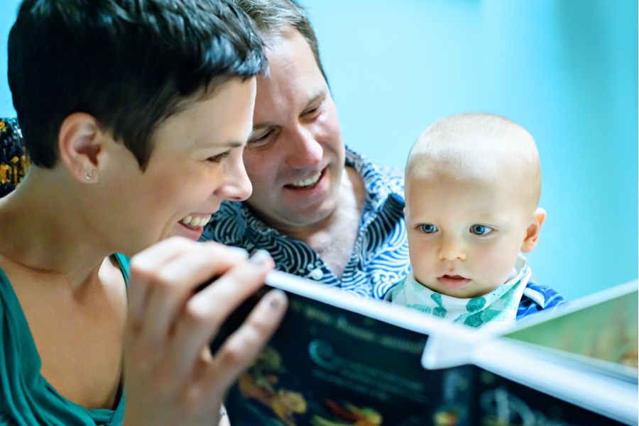 Two parents read a book to their one year old baby in thier documentary family photography session.