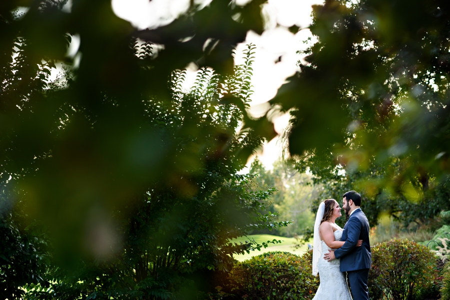 A bride and groom kiss under the fall leaves at The Manor House at Commonwealth Wedding.