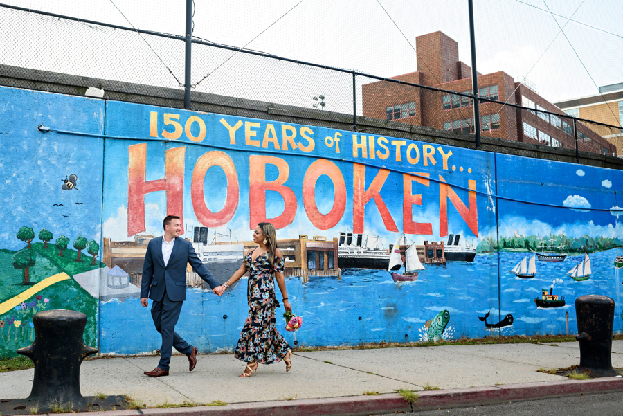 An Engaged couple walk in front of a Hoboken mural for thier engagement session.