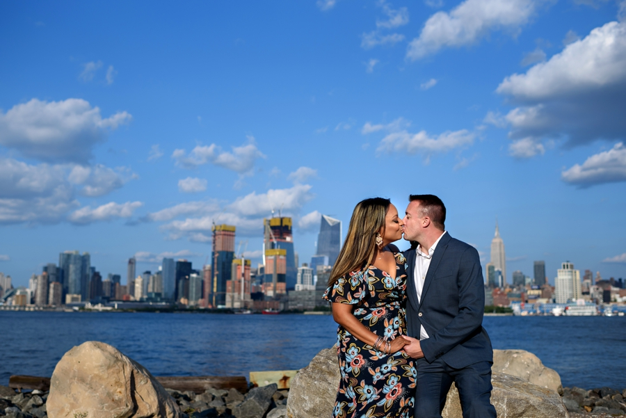 A couple sit on the rocks and kiss with NYC Skyline behind them.