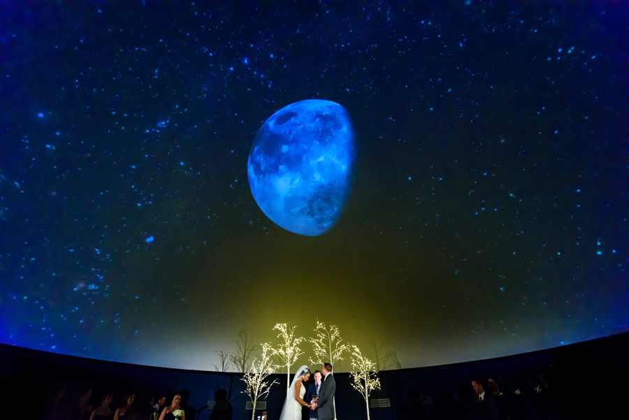 A wedding ceremony under the starry sky in the planetarium at the Franklin Institute in Philadelphia.